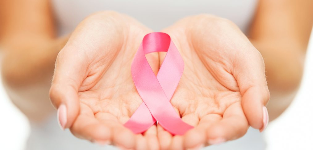 Woman holding a breast cancer ribbon