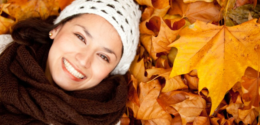Woman dressed for fall weather laying in a bed of fall leaves