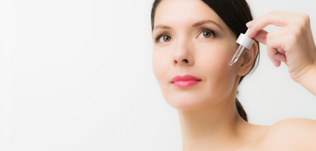Woman with dropper applying anti-aging skin care