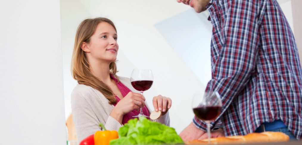 Couple cooking and drinking red wine for good health