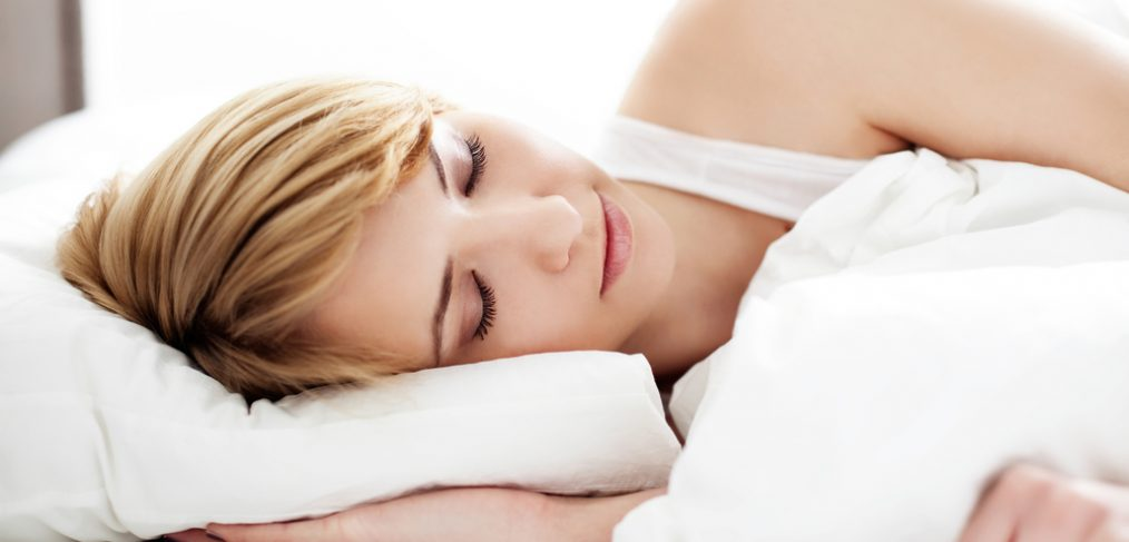 Woman in white clothes sleeping on a bed.