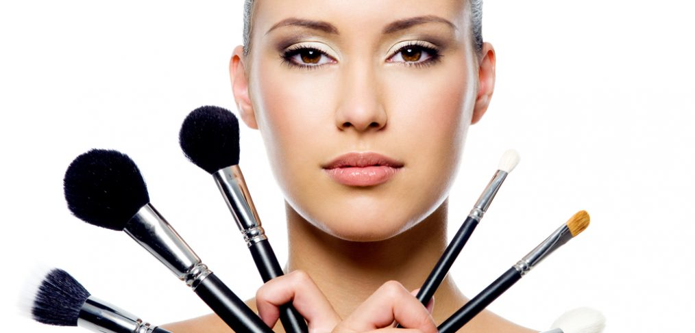 Woman holding different makeup brushes in her hands.