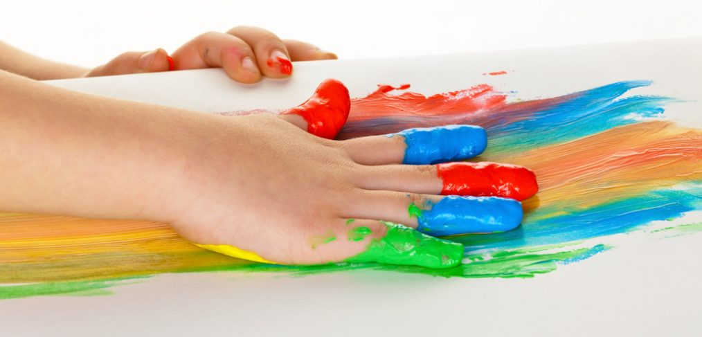Child painting different colors on a sheet of paper.