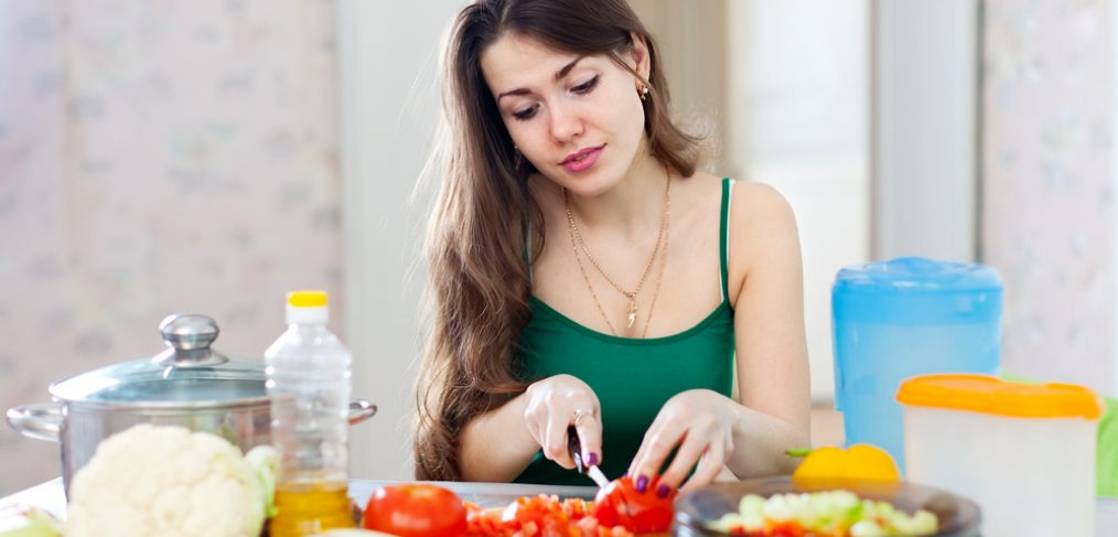 Woman cutting tomatoes while cooking