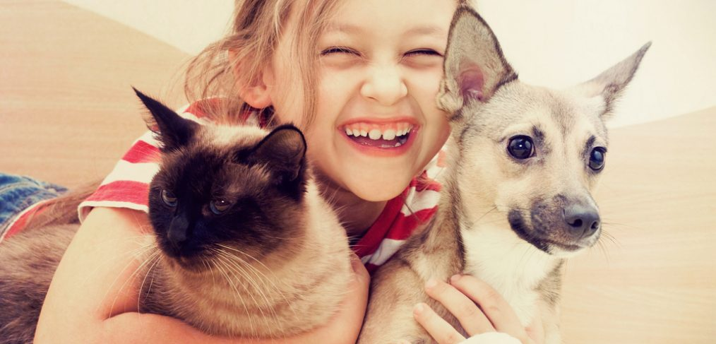 Young girl holding cat and dog