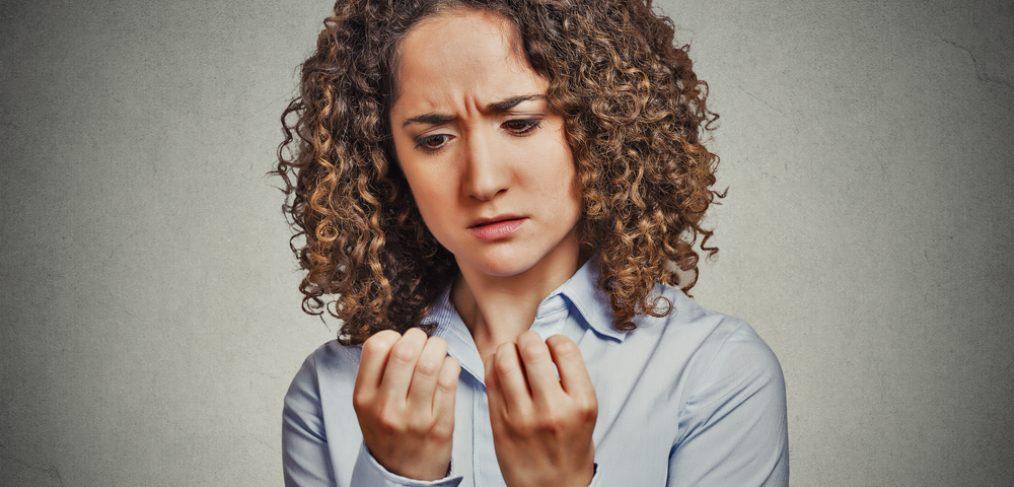 Woman looking at finger nails