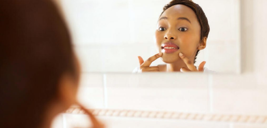 Woman looking at her skin in bathroom mirror