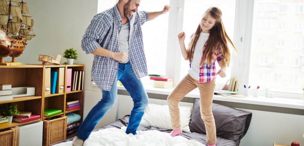 Father and daughter dancing on bed