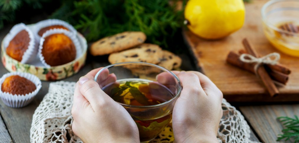 Woman's hands holding cup of green tea