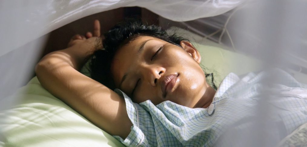 Woman sleeping in a mosquito net