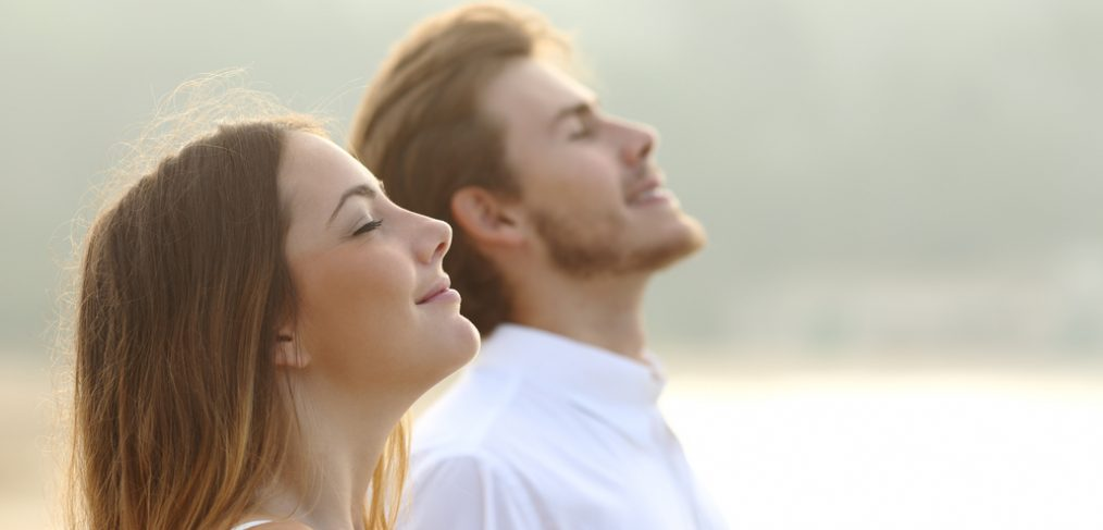 Couple breathing deeply outdoors