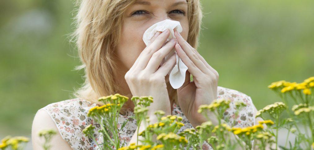 Woman sneezing into napkin outside