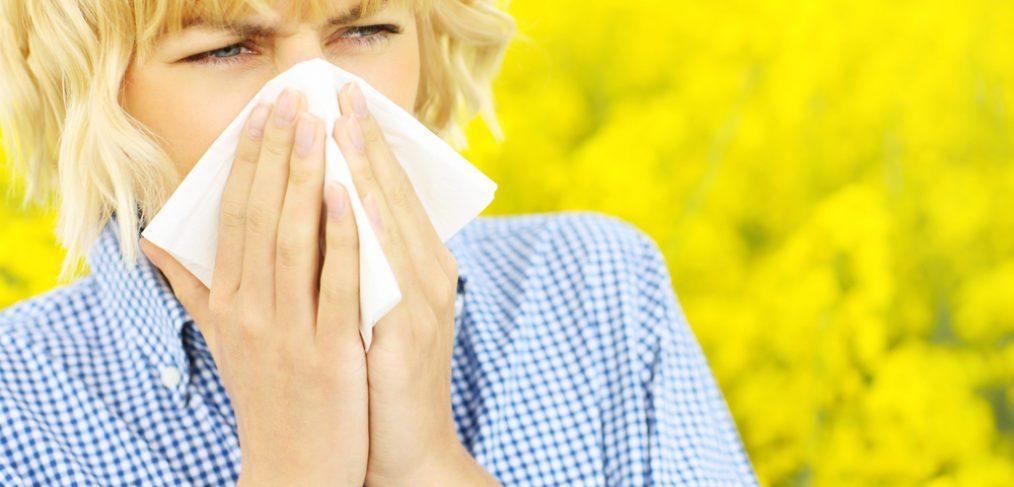 Woman sneezing into white napkin