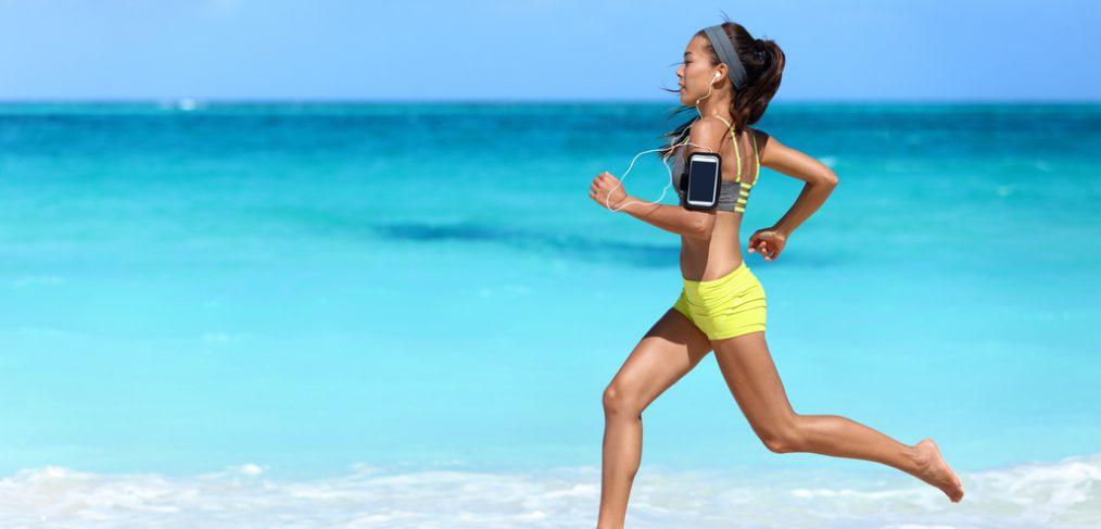 Woman running barefoot on beach