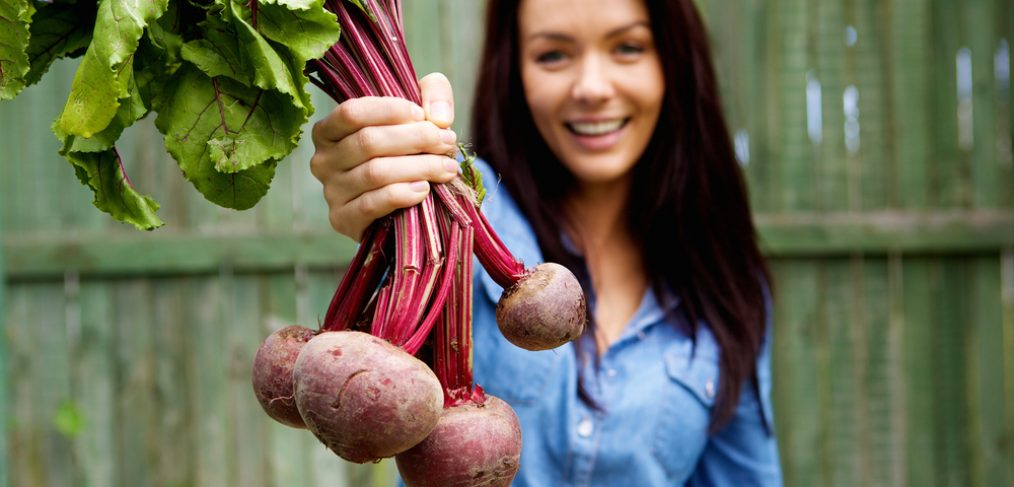 Woman holding up fresh beetroot