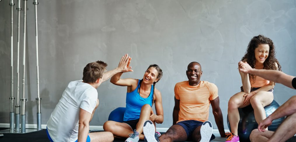 Workout friends high-five each other, resting