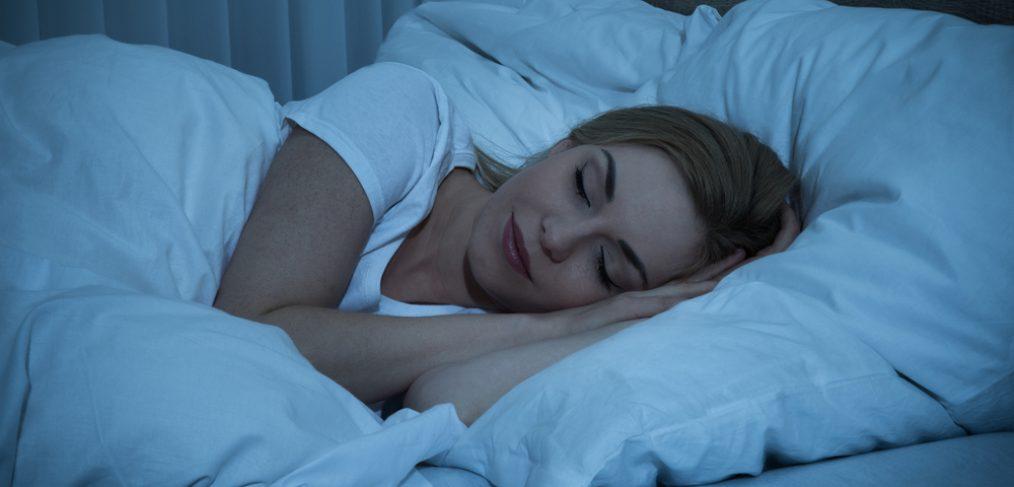 Woman sleeping in low-lit room