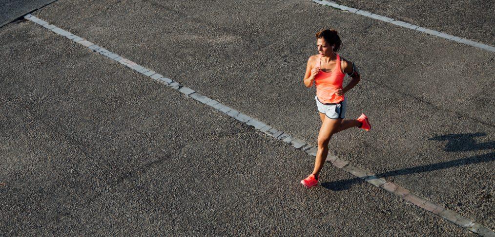 Woman running across track