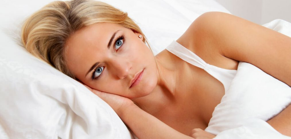 Unhappy woman lying awake in bed