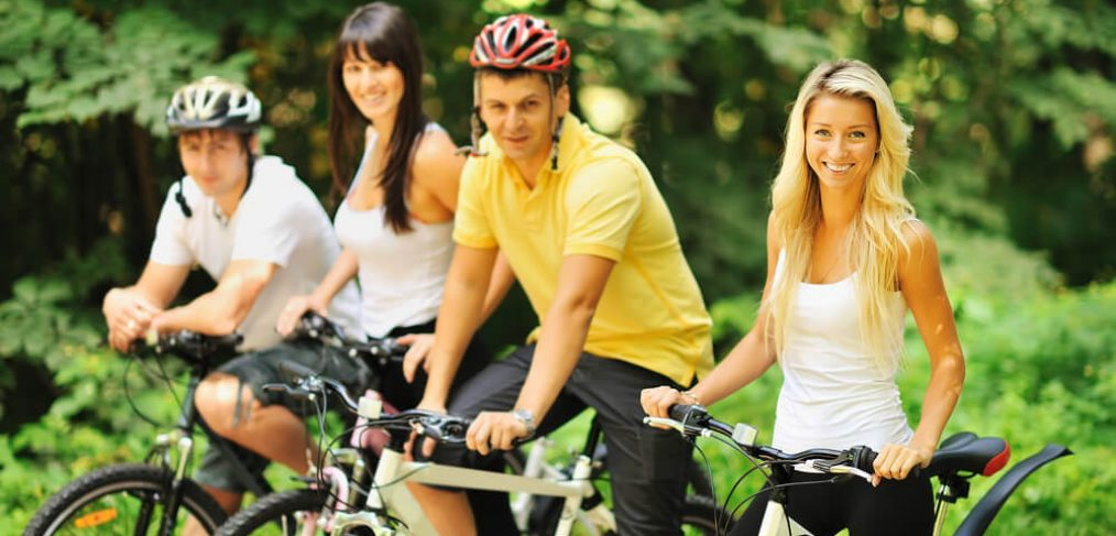 Young people cycling together in the park
