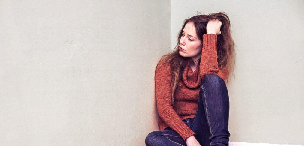 Sad woman beside wall