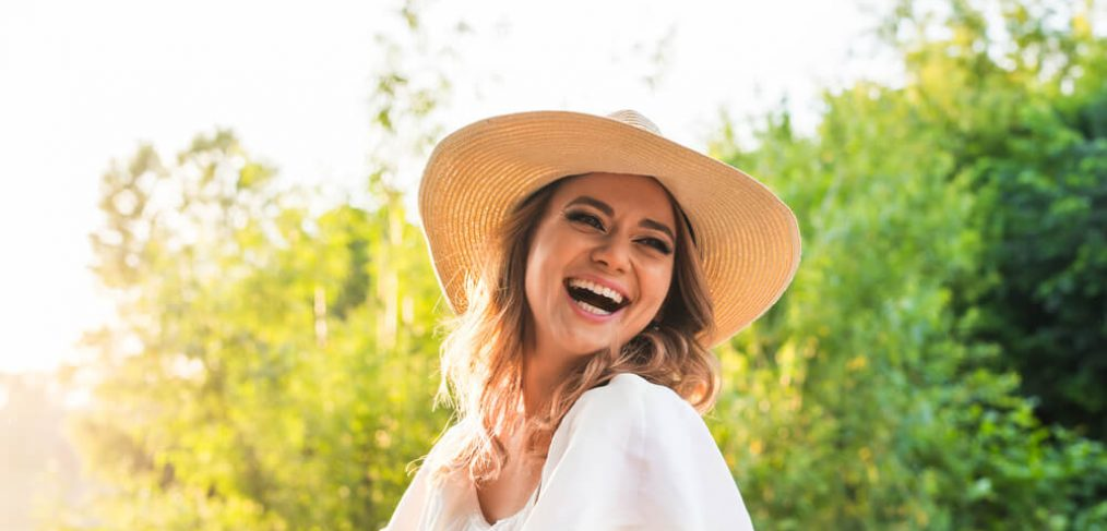 Woman with hat laughing outdoors