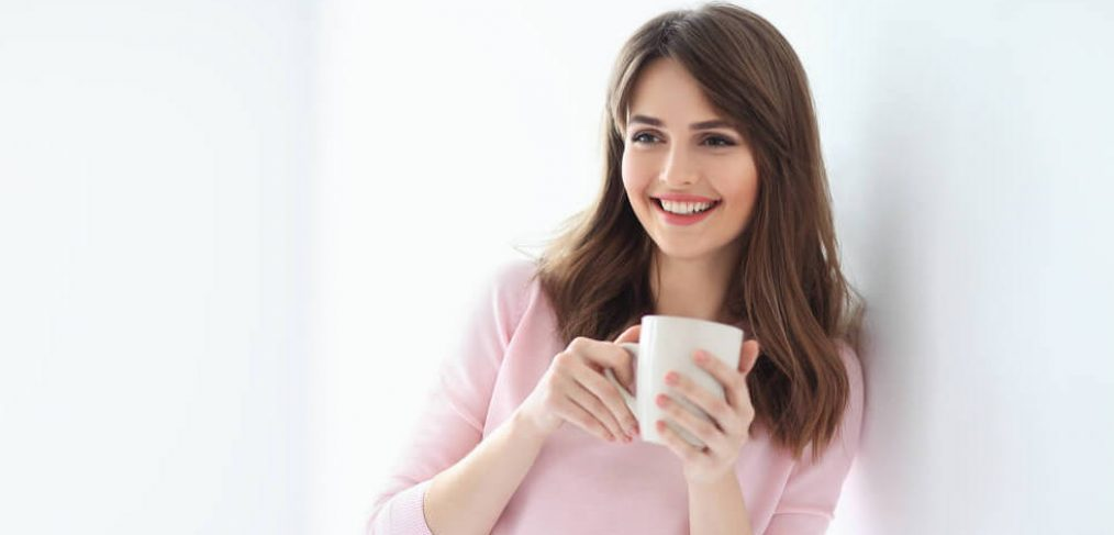 Smiling woman nursing a cup of tea