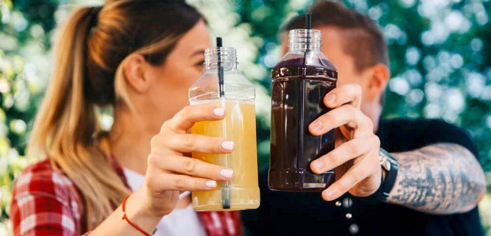Couple holding up bottled juices