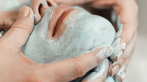 Closeup of woman enjoying facial mask treatment
