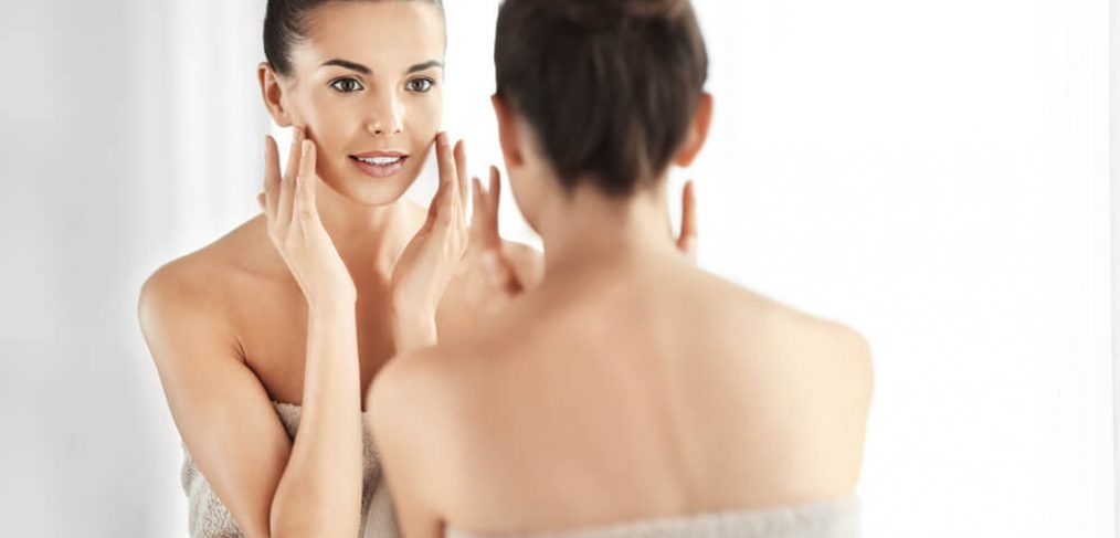 Woman checking skin in mirror