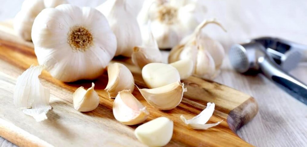 Whole garlic and garlic cloves on a wooden chopping board