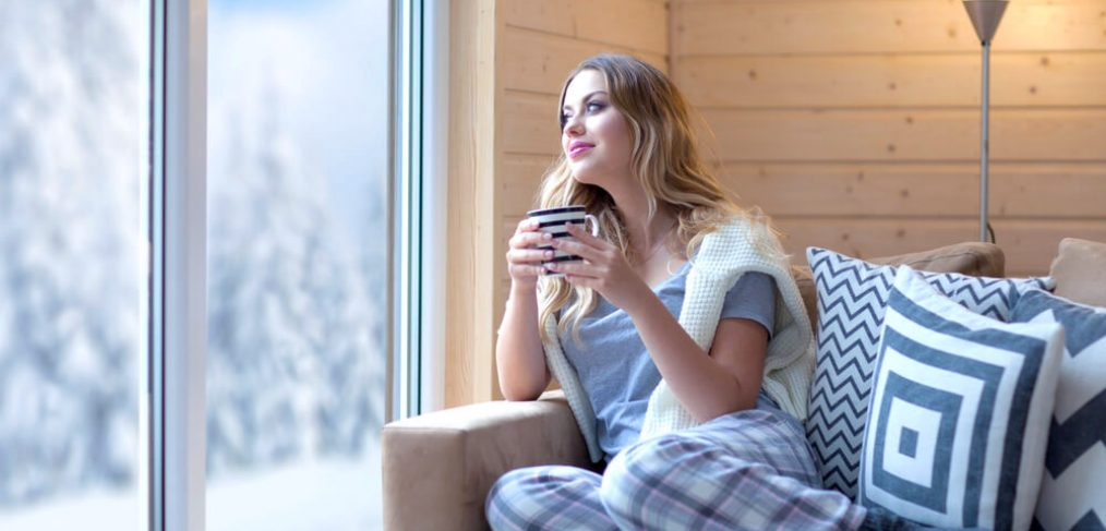 Smiling woman enjoying coffee indoors on a winter day
